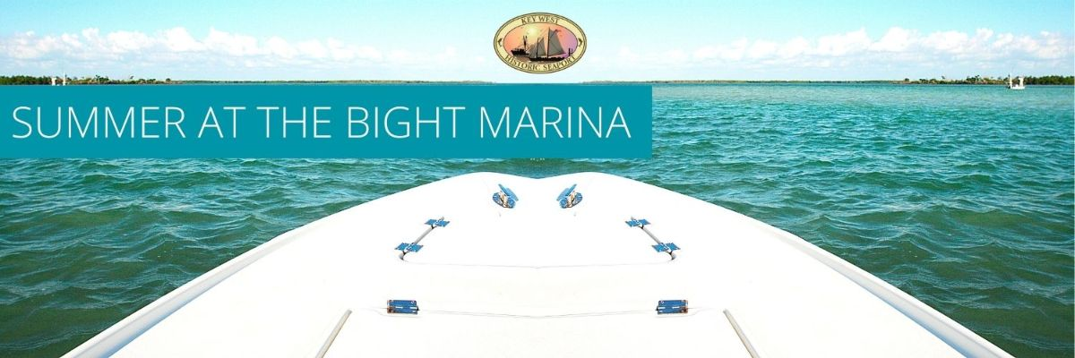 the front part of a boat extending out into the cool blue ocean water with a key west historic seaport logo on top.